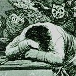 a man slumped on his desk, from 'The Sleep of Reason Produces       Monsters'